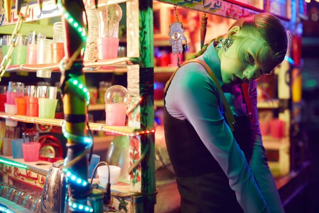 Urban Downtown, Model wearing a Patrizia Pepe shirt, Jumpsuit by Sportmax and earrings from Cairo Boutique. Half body cropped the model staring at the camera with green lights.Qatar Airways, Photography Toufic Araman Styling Anna Castan Tomas Hair and Mak